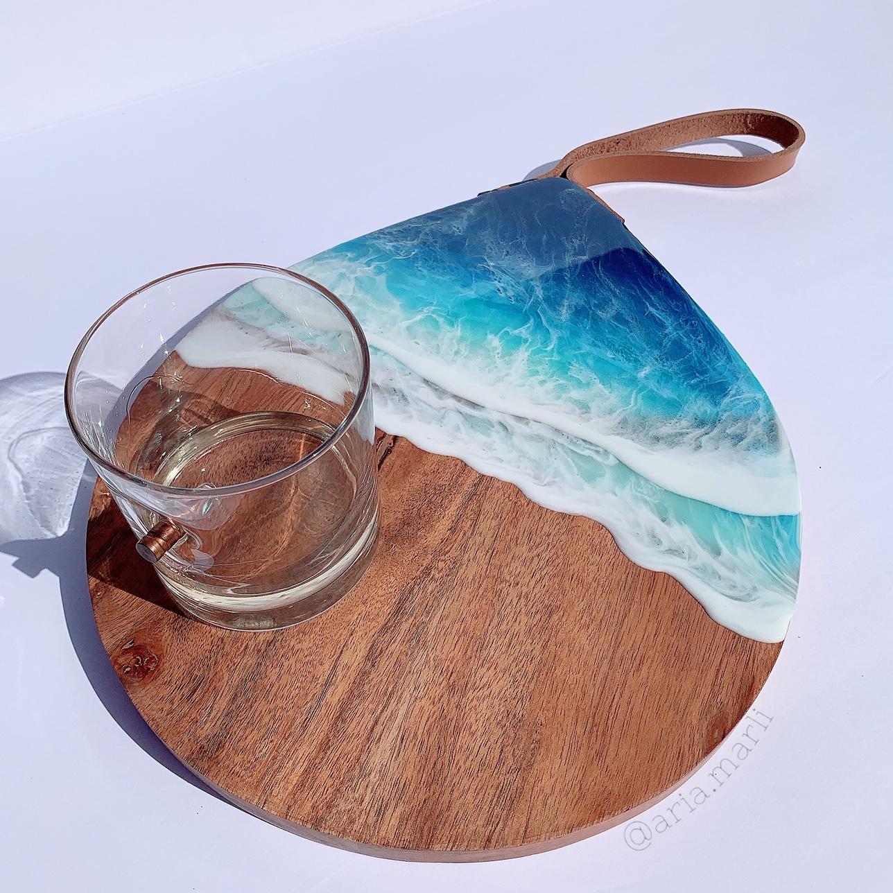Wood serving board with ocean wave coating of resin