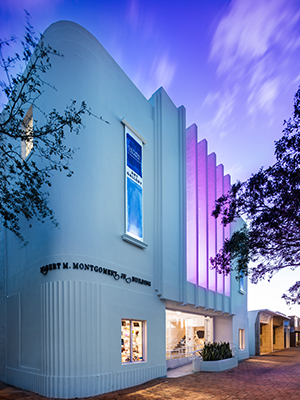 Two story white art deco building at sunset with purple lighting on facade