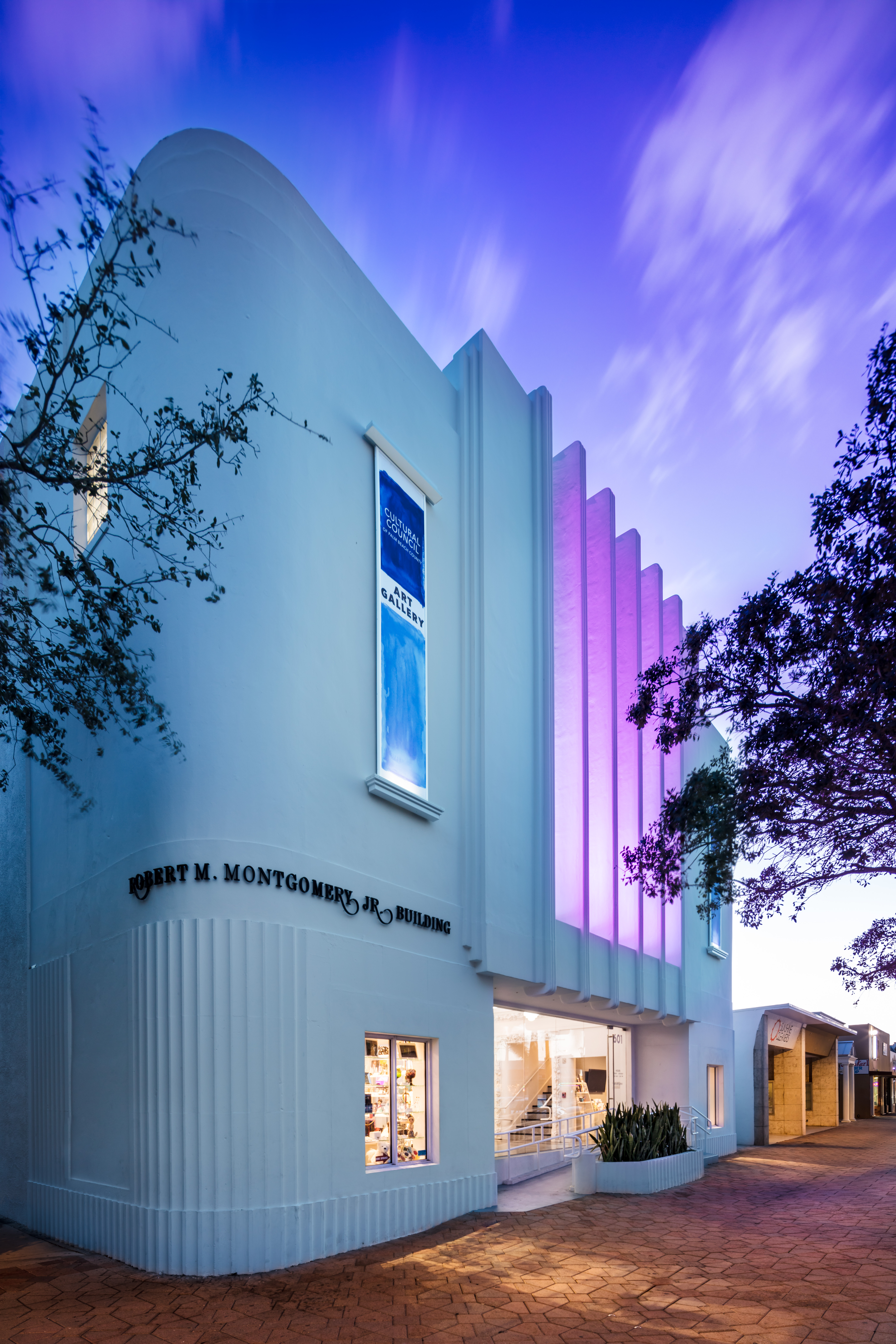 Evening photo of art deco facade of Cultural Council building in Lake Worth Florida with purple uplighting