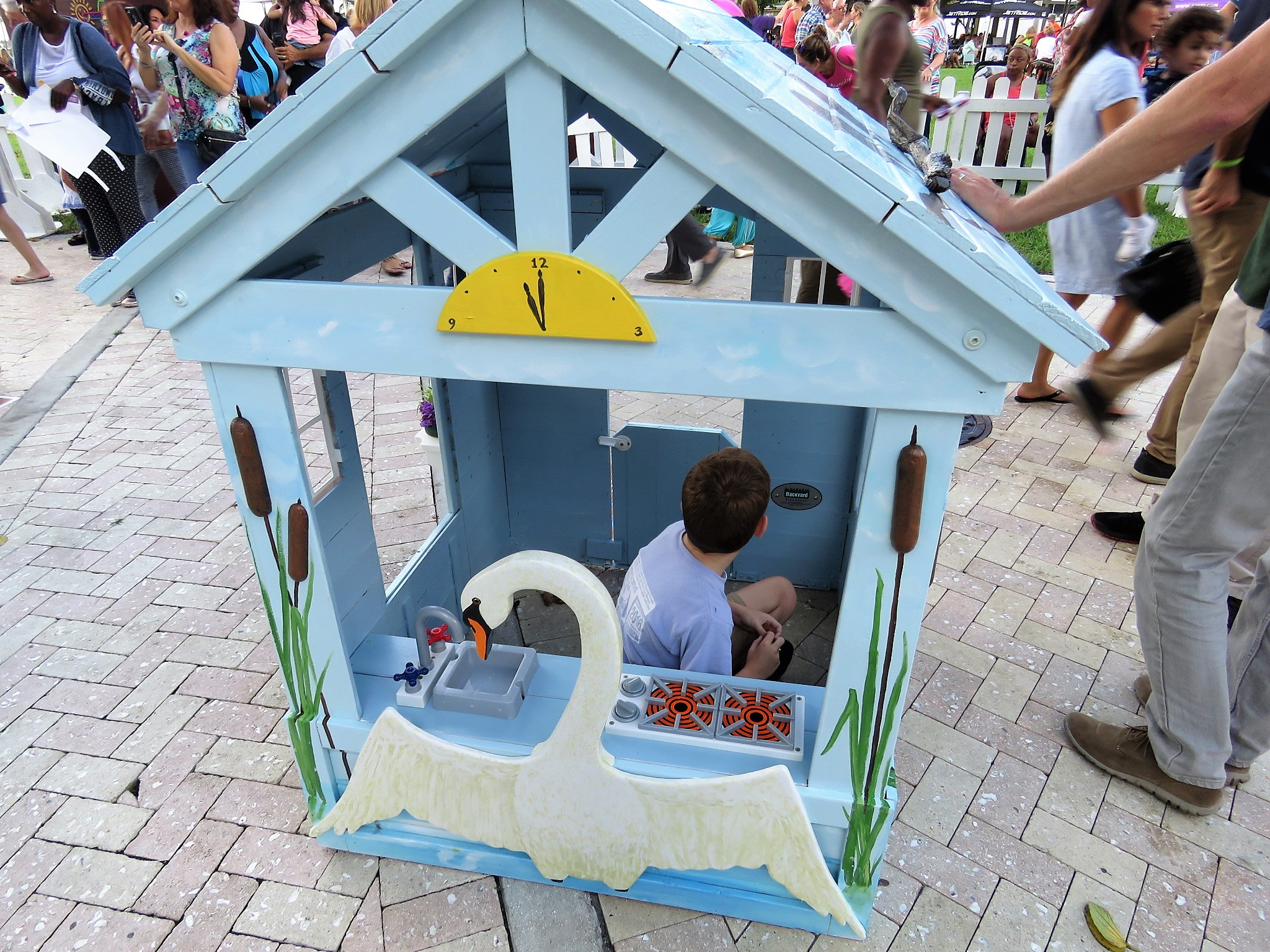 Boy plays in blue playhouse decorating with swan from The Ugly Duckling