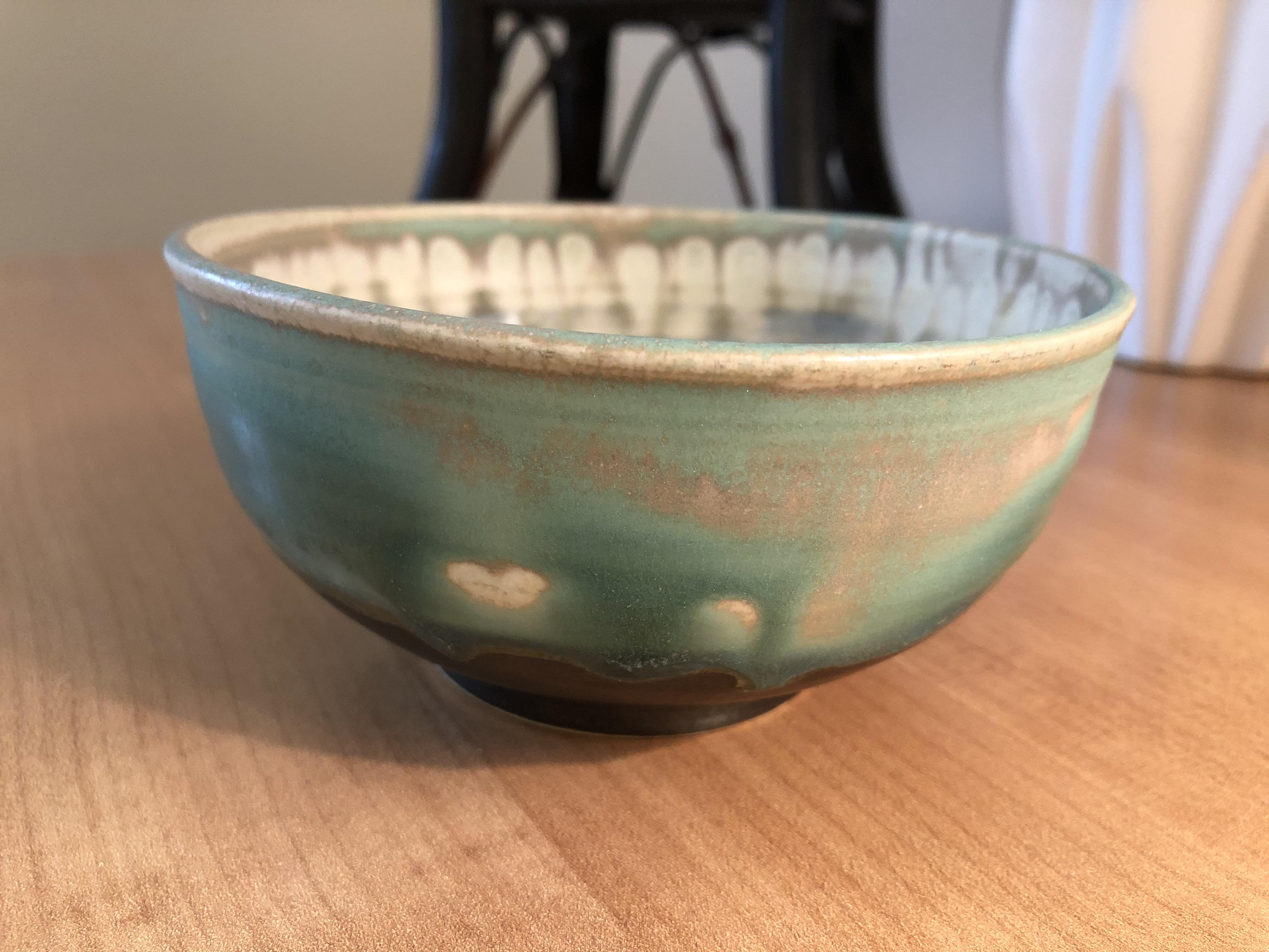Aqua, brown and gray handmade pottery bowl on table