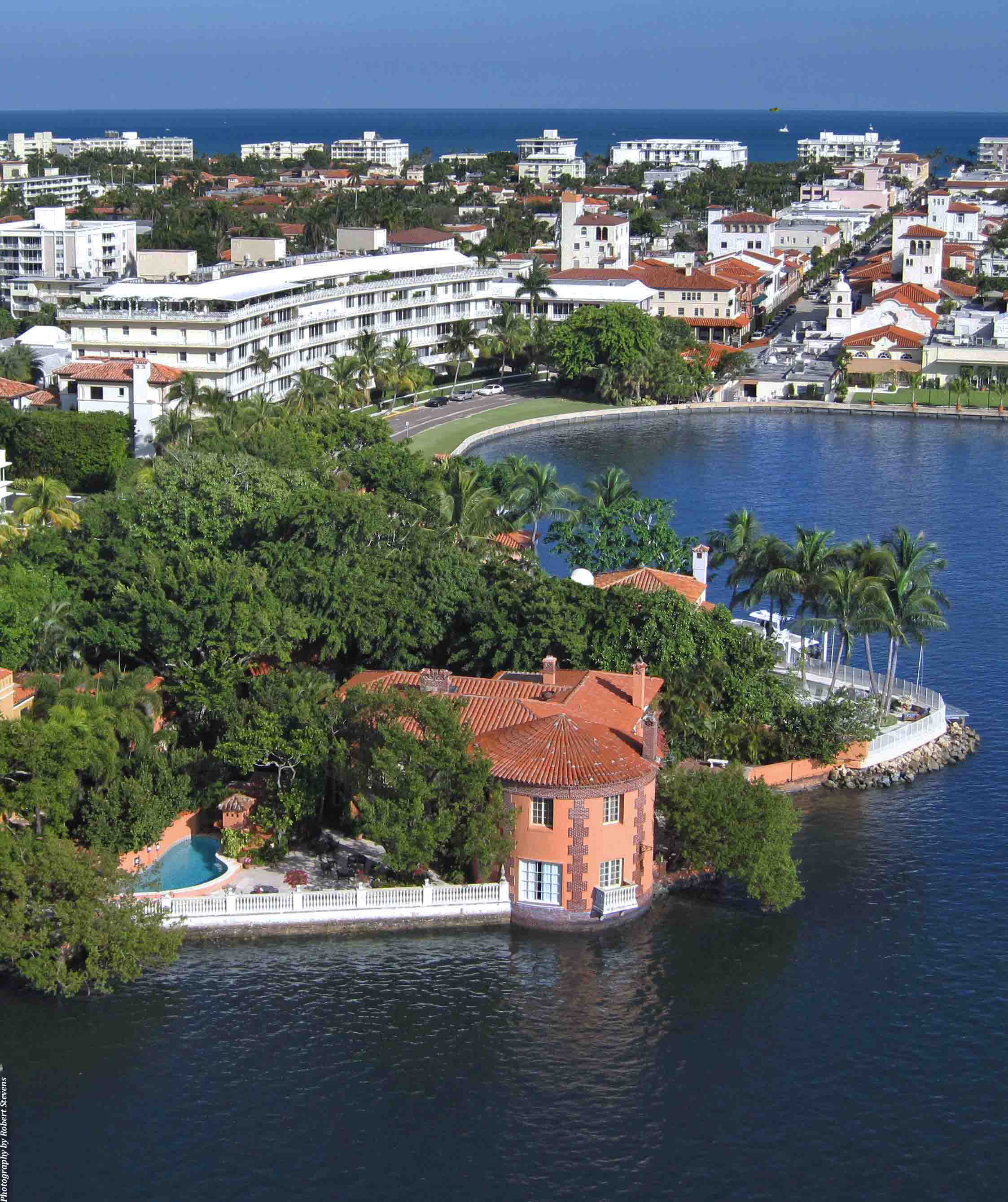 Aerial view of terracotta colored estate lakefront Palm Beach with condos and ocean in background