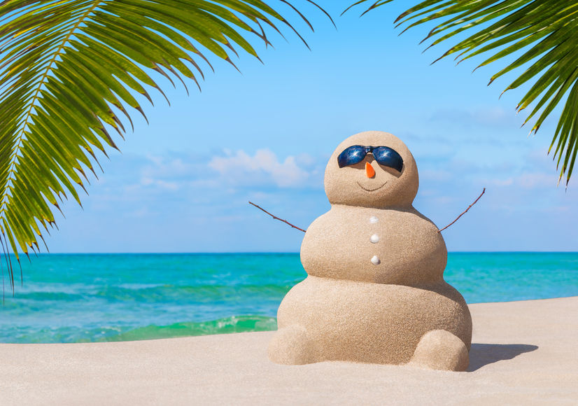 Snowman made of sand wears sunglasses with aqua blue ocean and palm trees in background