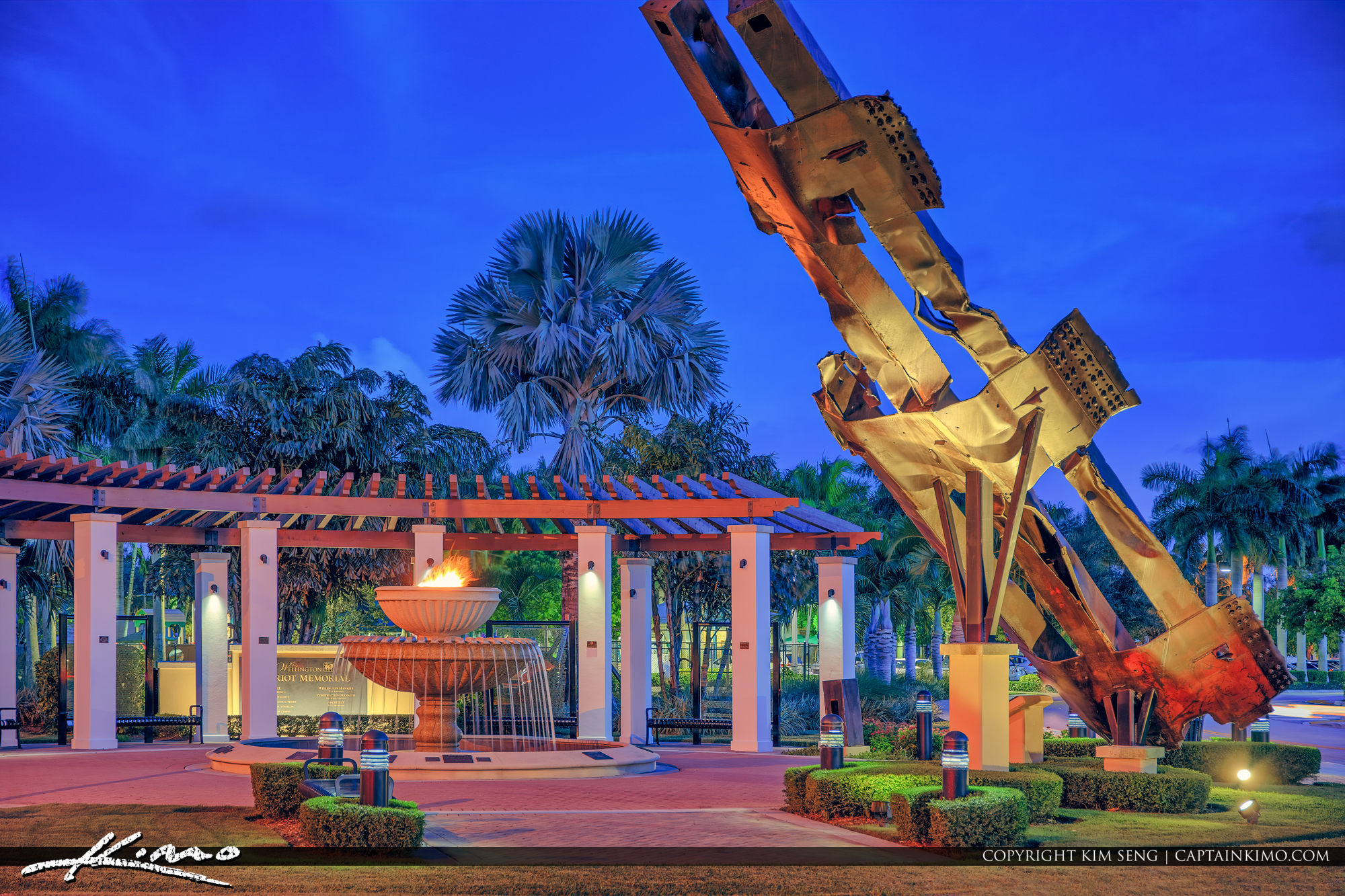 Large metal beam sculpture next to eternal flame fountain and pavilion