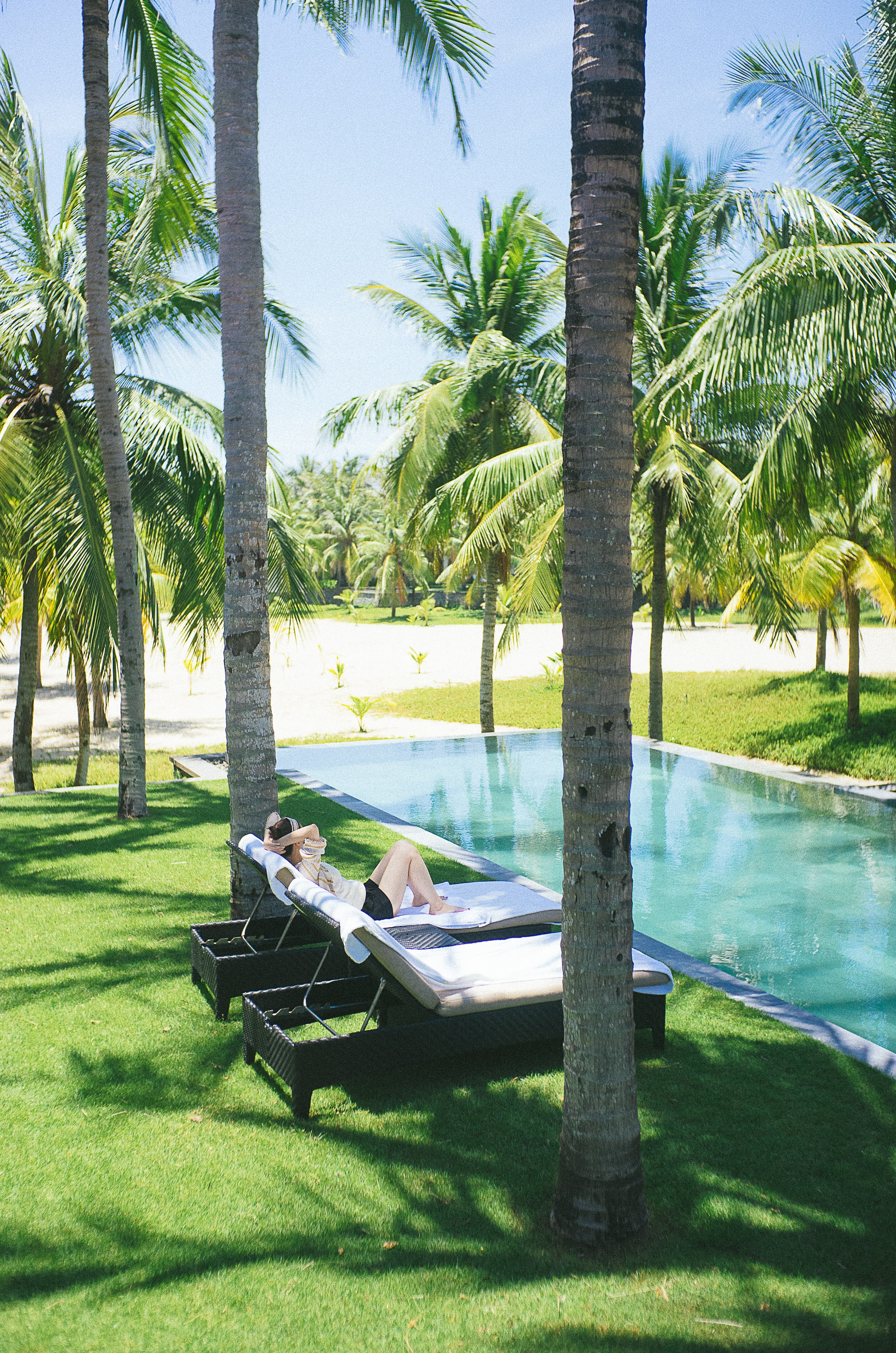 Woman reclining on lounge chair poolside under palm trees