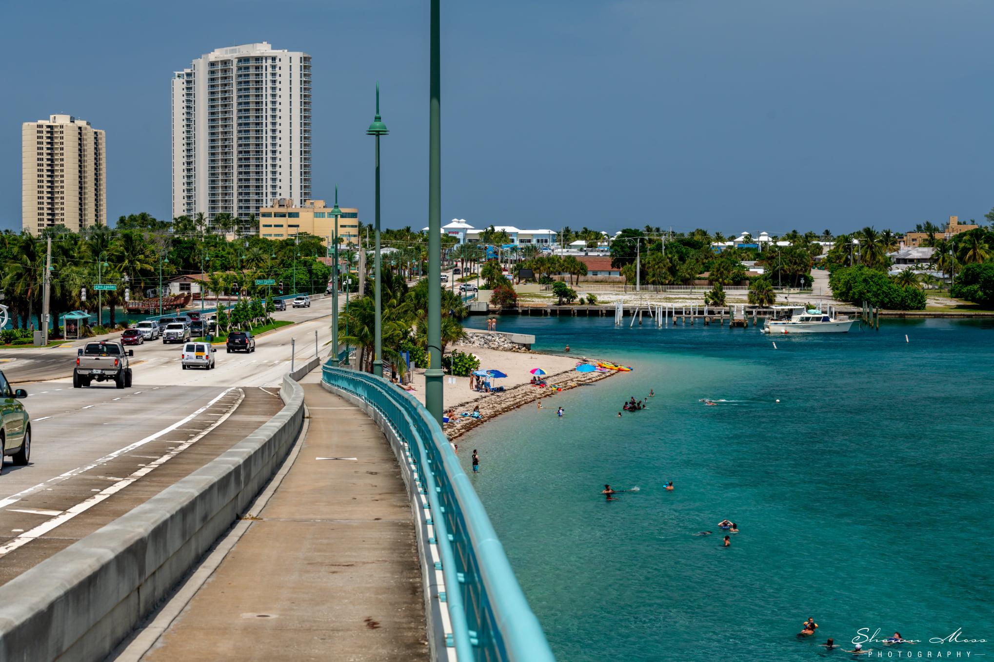 Snorklers in aqua water from top of bridge