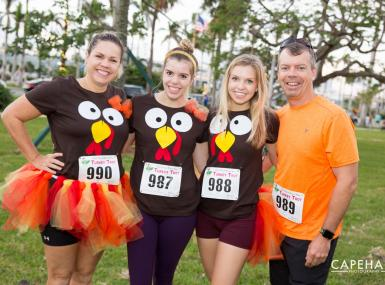 Four runners pose in turkey outfits before Turkey Trot 5K Palm Beach
