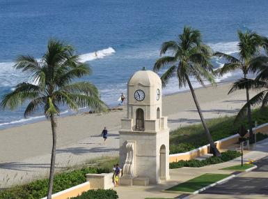 Famous Worth Avenue clock tower in Palm Beach with ocean, sand and palm trees