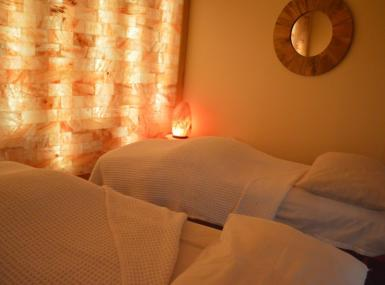 Room features Pink Himalayan salt wall backlit with two massage tables