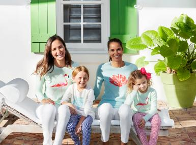 Two women and two young girls on lounge chair in J.McLaughlin pastel sweaters sporting tropical motifs of coral, sea turtles and flamingos