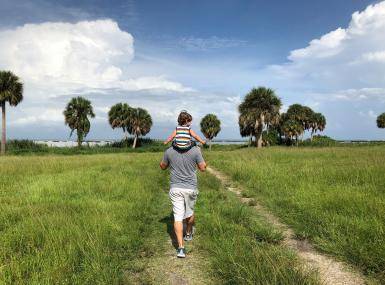 Man hikes in natural grassy area with young son on shoulders