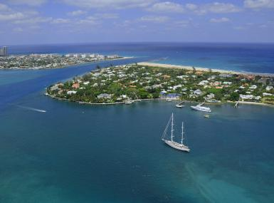 Aerial photo of Palm Beach Inlet features sailboat heading out to sea from Lake Worth Lagoon