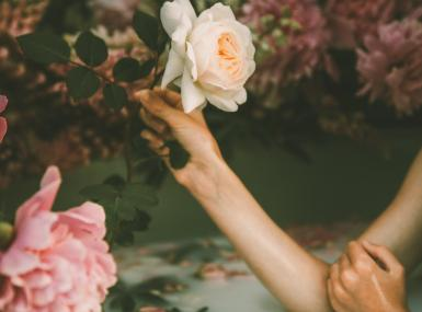 Women soaking in garden bath surrounded by large pink peonies