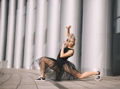Ballerina in black tutu and sneakers poses in front of large columns in contemporary street setting