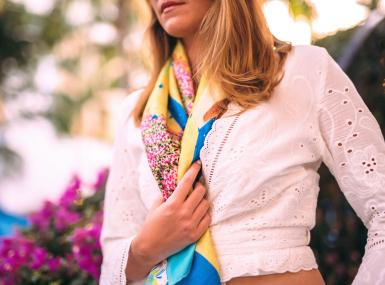 Blond woman in white blouse with turquoise, yellow and pink silk scarf around neck