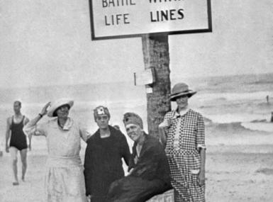 1920s swimmers stand in front of Safety Sign on beach