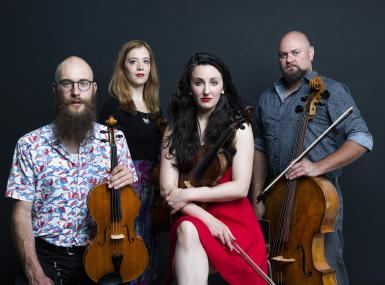 string quartet pose with instruments in casual dress