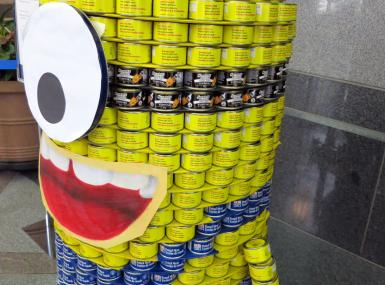Giant yellow and blue cartoon minion assembled from cans of food
