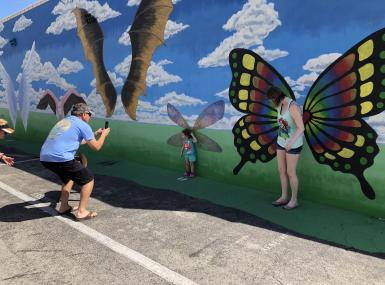 Child and adult pose in front of wall painted with giant butterfly wings