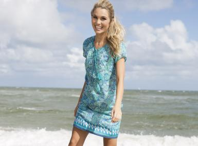 Model wearing bella tu cap sleeved shift dress in turquoise pattern stands at ocean's edge on a stormy day