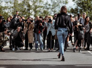 Model in jeans walks toward throng of photographers and paparazzi