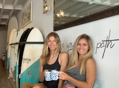 Two blond women sit with coffee mugs in front of custom surfboards