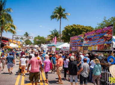 Crowd of people enjoying food and art booths at street festival in Delray Beach