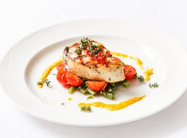 White plate with grilled fish steak over vegetables