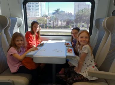 Four young girls smile for camera seated at table on commuter train