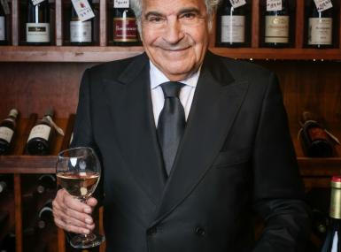 Monsieur Maurice Amiel proprietor of The French Wine Merchant in Palm Beach holds glass of wine in his store