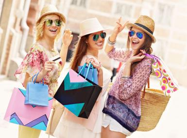Three young women with straw hats and shopping bags on city street