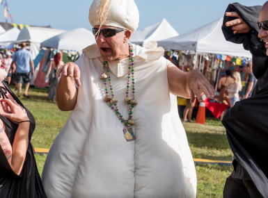 Man in garlic costume mock kills man and woman vampire with white festival tents in background