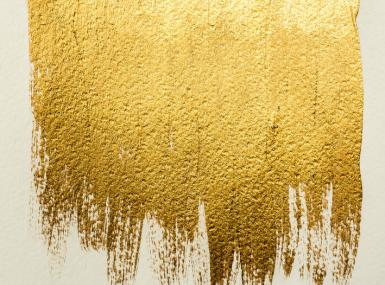 Gold metallic paint brushstroke on white paper