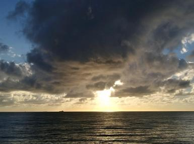 Dark storm cloud over an ocean sunrise