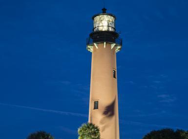 Jupiter lighthouse uplit with navy blue night sky as backdrop