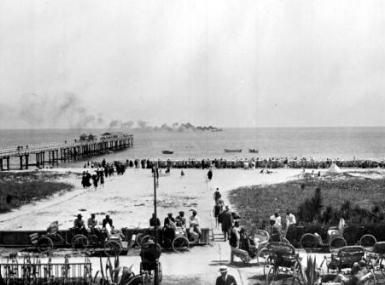 Black and white photo of spectators on beach watching wooden train pier and steamship off the coast