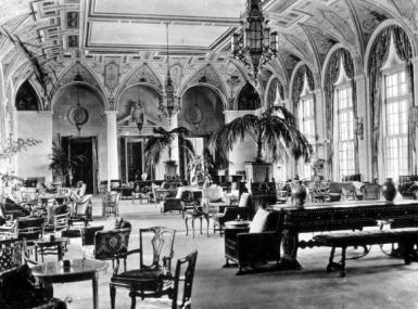 Black and white photo of 1920s hotel lounge with arched windows and painted ceilings