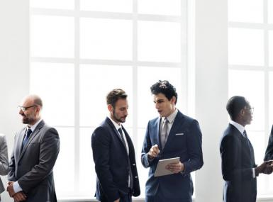 Men and women in business suits stand in small groups having discussions