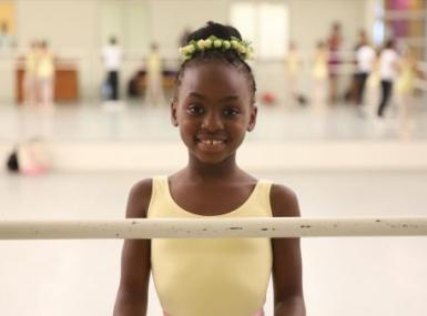 A young ballerina poses before the barre, wearing a yellow leotard and a circlet of yellow flowers in her hair
