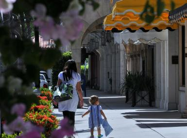 Mom and toddler walk along flower lined street of shops
