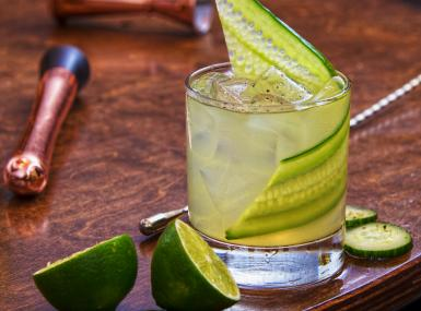 Cocktail glass with thin cucumber slice, ice and tequila