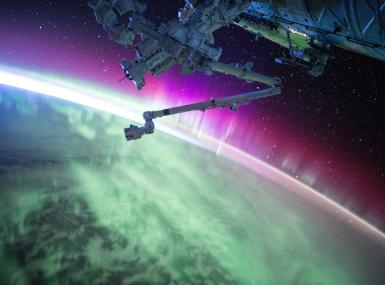 View of earth's green and fuchsia aurora borealis from International Space Station
