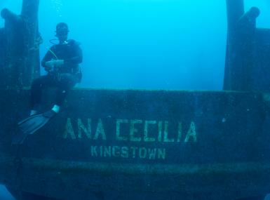 Diver underwater sitting on freighter wreck Ana Cecilia