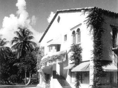 Black and white photo of Mediterranean style building with vines growing on it