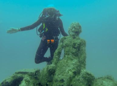 Aqua water with diver by mermaid statue covered in coral