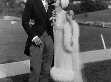Couple in 1920s wedding attire on golf course in front of club house