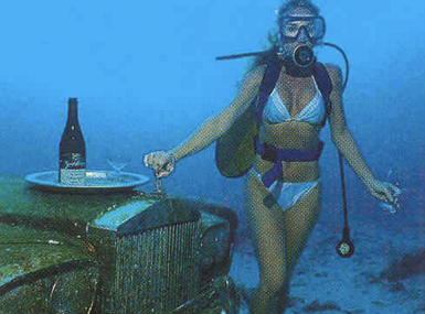 Bikini-clad diver stands beside a submerged Rolls Royce