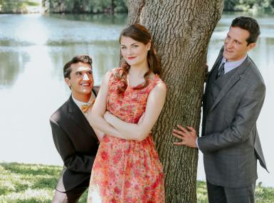 Two men in suits peak around tree trunk at young women in dress