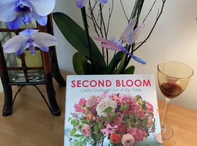 Coffee table with purple orchid, half finished wine glass with lipstick and book, Second Bloom: Cathy Graham's Art of the Table