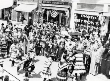Seminole Indians dancing in parade in downtown West Palm Beach with spectators standing in front of stores